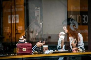 South Koreans drank coffee at a Dunkin' Donuts in Seoul. There are now more than 900 Dunkin's in the country.